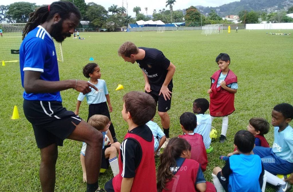 Coaches Yohance Marshall (L) and Matt Lawrey (C) speak with young players at the ATL FC training camp,St Mary's grounds, in St Clair yesterday.
