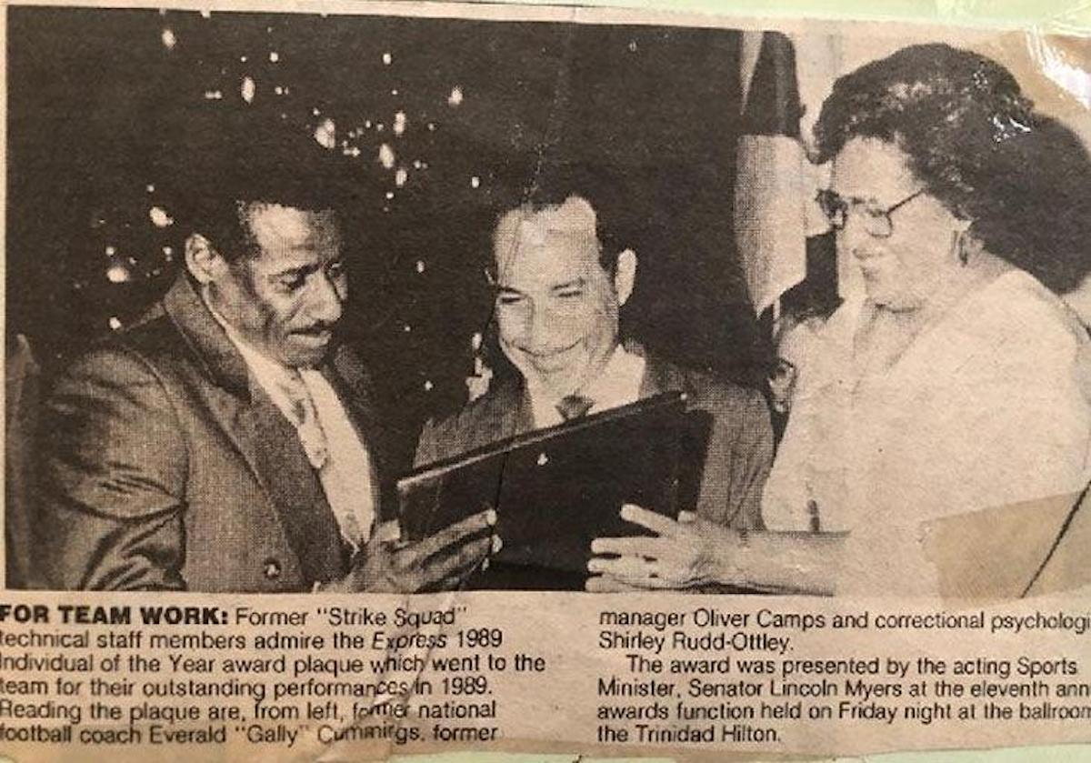 "FLASHBACK: From left, Strike Squad coach Everald ""Gally"" Cummings, manager Oliver Camps, centre, and team psychologist Shirley Rudd-Ottley admire the Express Individual of The Year award given to the team in 1989 for its effort in that year's World Cup qualifying campaign."