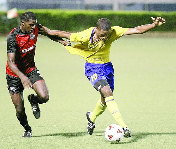 Keion Goodridge, left, of bmobile Joe Public pulls on the jersey of Defence Force's Kerry Joseph during their Toyota Classic quarterfinal at the Marvin Lee Stadium, Macoya on Tuesday night. Joe Public won 2-1. (Photo: T&T Guadrian)