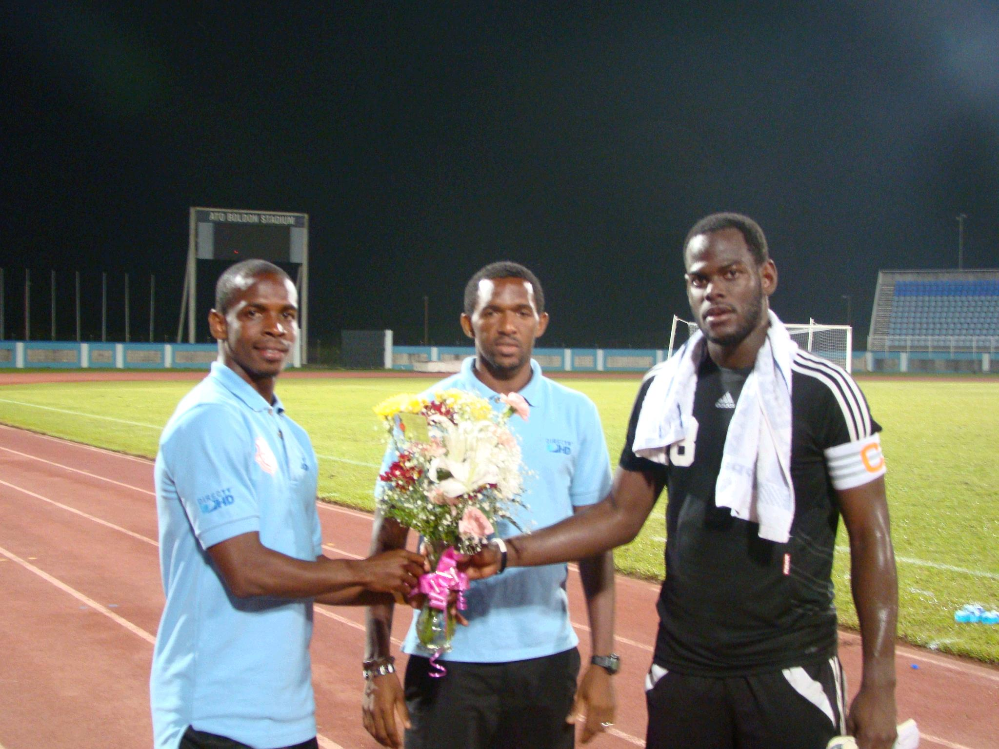 Lto R Antony Wolfe and Charles Pollard of North East Stars present Jan-Michael Williams with a bouquet for his fiancee, Candice Worrell.