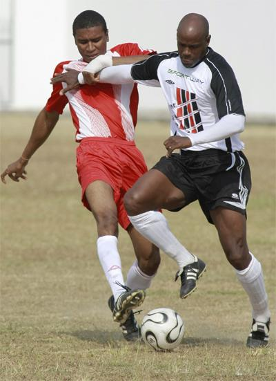 Derek Cave of Unit Trust, left, and Leonson Lewis of the Strike Squad battle for the ball during the launch of the Strike Squad's relief effort for Haiti labelled 'Haiti You Are Not Forgotten' on Saturday on Fatima grounds, Mucurapo.Photo: Anthony Harris