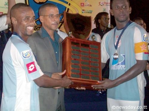 CAREY HARRIS, left, and Errol McFarlane, right, of North East Stars collect the Lucozade Sport Goal Shield Trophy from TT Pro League's CEO Dexter Skeene on Friday night. NE Stars beat San Juan Jabloteh 1-0 in the final. ...Author: JOEL BAILEY