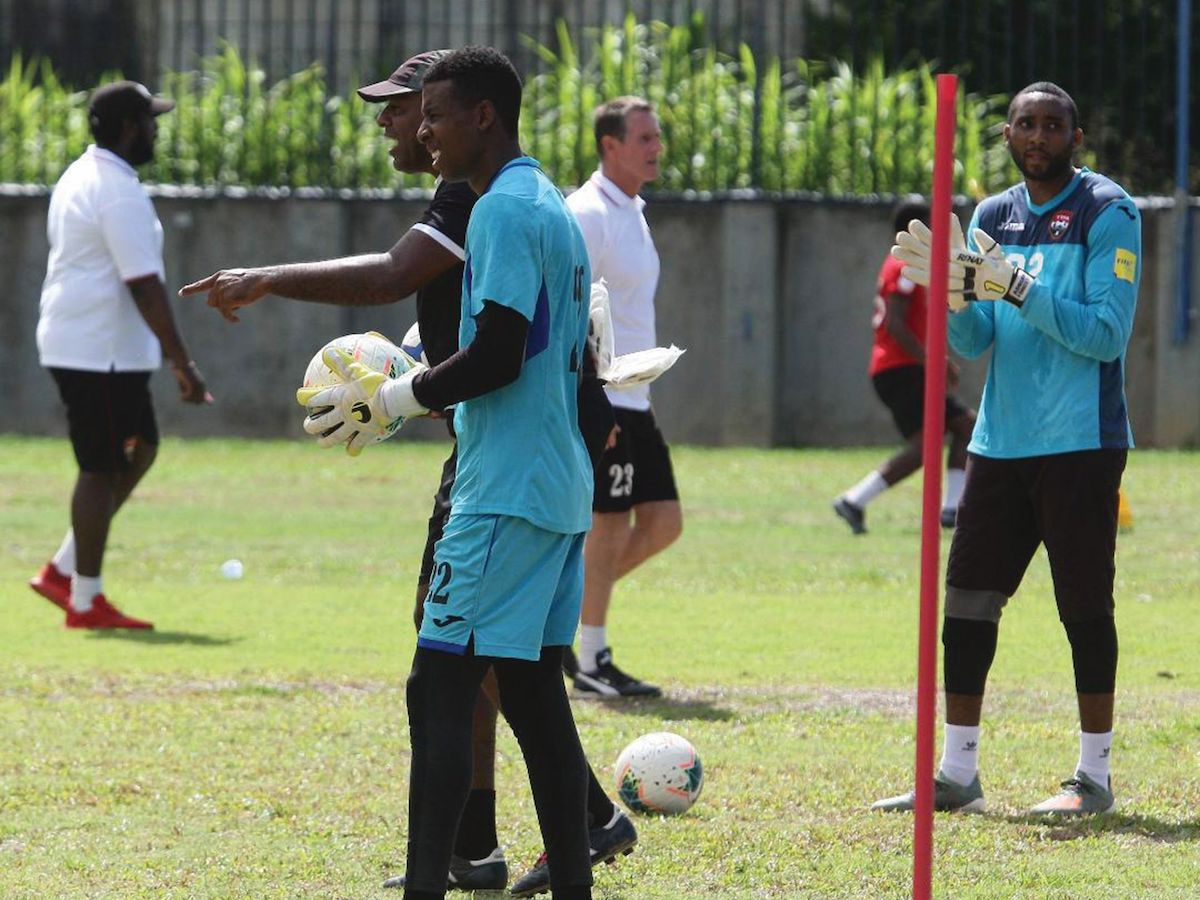 Goalkeeper Adrian Foncette, right, and Andre Marchan, centre, listen to instructions from the coaches Adrian Romain, left, Terry Fenwick, centre in background, and Keith Jeffreys at the training session for the senior national football team in June at the St James Barracks, Port-of-Spain. PHOTO: Anthony Harris