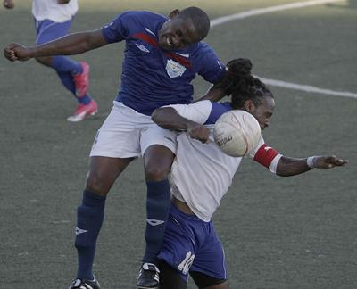 WASA's captain, Marvin Faustin climbs over the shoulder of Real Maracas captain, Shane Glasgow, in an effort to win the ball in their Emerald Apartments & Plaza Eastern Football Association League Cup final, at Marvin Lee Stadium, Macoya, on Sunday. WASA won 1-0. Photo: Anthony Harris